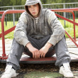 Young Man Sitting In Playground - Foto Stock