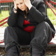 Foto Stock: Young WomSitting In Playground
