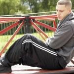 jovem sentado no parque infantil — Foto Stock #4796777