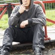 Young Man Sitting In Playground Smoking Joint - Стоковая фотография