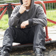 Young Man Sitting In Playground Smoking Joint - Stockfoto