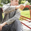 Young Man Sitting In Playground Drinking Beer - Stock Photo