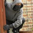 Young Man Breaking Into House - Stock Photo