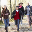 Family Running Through Autumn Countryside — Stock Photo
