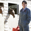 Portrait Of Vet Standing By Horse Stables - Stock Photo