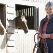 Senior Woman Standing By Stables — Stock Photo #4797379