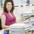 Woman sitting happily at her desk — Stock Photo