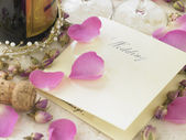 Wedding Invitation Next To Champagne Bottle Surrounded By Flower — Stock Photo
