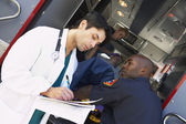 Hospital doctor taking notes as paramedics arrive with patient — Stock Photo