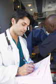 Doctor taking notes as paramedics unload patient — Stock Photo