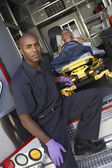 Male paramedic preparing to unload patient from ambulance — Stock Photo