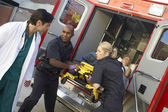 Paramedics and doctor unloading patient from ambulance — Stok fotoğraf