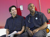 Two paramedics cheerfully doing paperwork, sitting by their ambu — Stock Photo