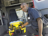 Paramedic removing empty gurney from ambulance — Stock Photo
