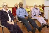 Adultos idosos em uma aula de alongamento — Foto Stock