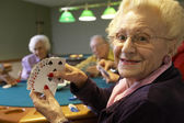 Senior adults playing bridge — Stok fotoğraf
