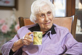 Senior woman drinking hot beverage — Stock Photo