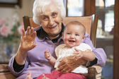 Grandmother holding her granddaughter on lap — Stock Photo