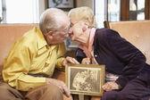 Senior couple holding wedding photo — Stock Photo