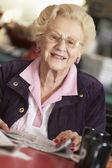 Senior woman reading newspaper — Stock Photo