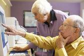 Senior woman helping senior man use computer — Stockfoto