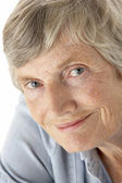 Portrait of senior woman smiling at the camera — Stock Photo