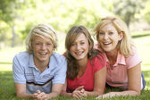 Woman And Her Teenage Children Lying On Grass — Stock Photo