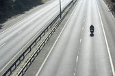 Lone Biker On An Empty Highway — Stock Photo