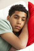 Young Boy Looking Sad On Sofa — Stockfoto
