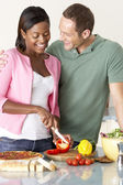 Young Couple Preparing Meal In Kitchen — Stock Photo