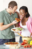 Young Couple Eating Meal In Kitchen — Stock Photo