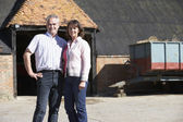 Farmer And Wife Standing In Front Of Farm Buildings — Stock Photo