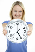 Woman Holding Clock Showing 5 O'Clock — Stock Photo