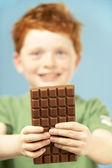 Barra di tenuta giovane ragazzo del cioccolato — Foto Stock