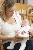 Mother Reading Story To Baby In Nursery — Stock Photo