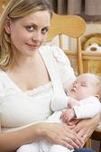 Matka držení dítěte v dětském pokoji — Stock fotografie