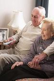 Pareja senior en casa viendo la tele — Foto de Stock