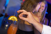 Man Drugging Woman's Drink In Bar — Stock Photo