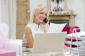 Woman using laptop and talking on phone — Stock Photo