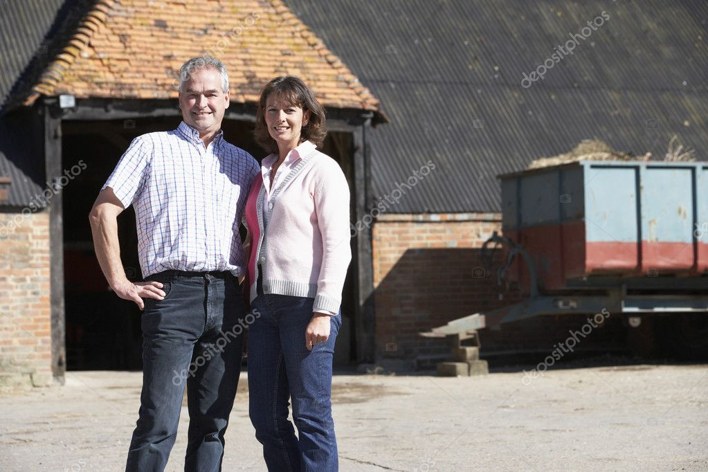 Farmer And Wife Standing In Front Of Farm Buildings — Stock Photo #4795903