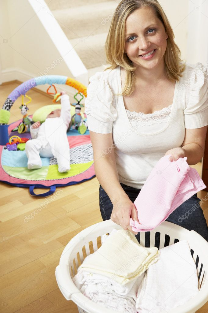 Mother Folding Baby Clothes At Home — Stock Photo #4796395