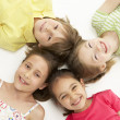 Circle of four young friends lying down smiling — Stock Photo
