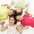Circle of four young friends smiling and holding hands — Stock Photo