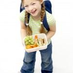 Studio Portrait of Smiling Girl Holding Lunchbox — Stock Photo