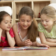 Three Young Girls Reading Book at Home — Stock Photo #4814445