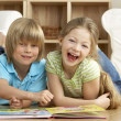 Two Young Children Reading Book at Home — Stockfoto
