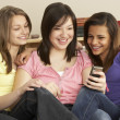 Teenage Girlfriends Reading Mobile Phone at Home — Stock Photo