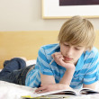 Stock Photo: Teenage Boy Writing In Diary In Bedroom