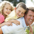 Stock Photo: Father giving children piggyback