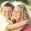 Stock Photo: 2 Children hugging outdoors